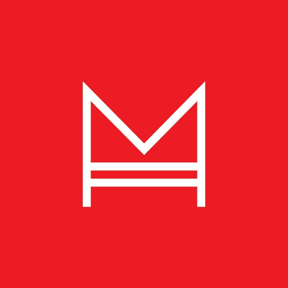"""This logo consists of a bright red square, which has, in the middle, a white outline of a capital """"M"""" with two horizontal lines connecting the interior vertical lines of the """"M."""""""