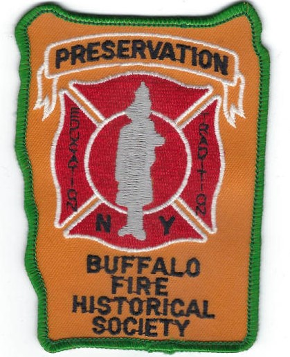 """This is a patch with a green thread border and an orange background. At the top, in a white-outlined banner graphic, is the word """"Preservation."""" In the middle is a red fire emblem, bisected by a grey silhouette of a firefighter. On either side are the words """"education"""" and """"tradition"""" in vertical black lettering. On either side of the silhouette's feet are the letters """"N"""" and """"Y."""" At the bottom are the words """"Buffalo Fire Historical Society' in black."""