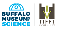 """On the right is a logo which reads, in blue, """"Buffalo Museum of Science,"""" with the outline of a dome/planetarium above it. The image is divided by a vertical grey line. On the right is a logo whose words at the bottom, in brown, read """"Tifft Nature Preserve."""" Above that is a green drawing of a plant with two leaves and a long top, surrounded on each side by a brown rectangle with a notch out of the top."""
